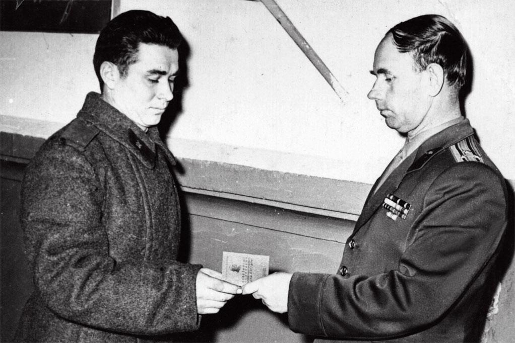 Начальник политотдела дивизии вручает комсомольский билет Кодинцеву Н.И.